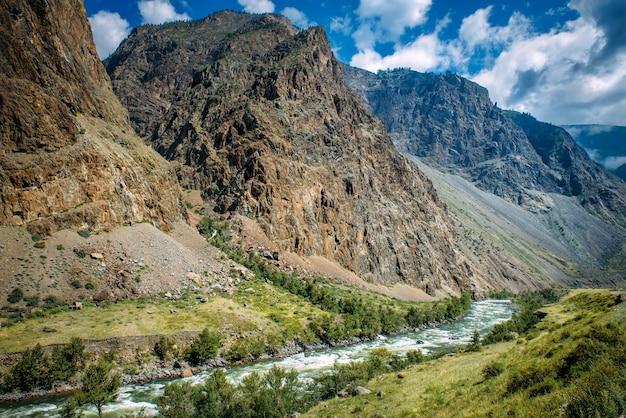 Rio entre as altas montanhas. paisagem pitoresca de montanhas rochosas de altai e o rio chulyshman. cordilheira, rio, costa verde, céu azul e nuvens brancas