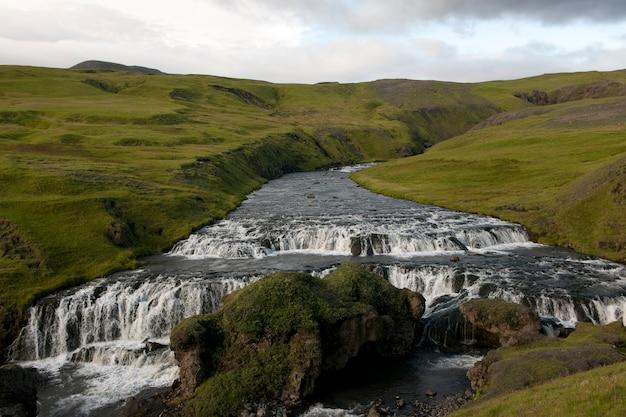 Rio erodido em pastagens montanhosas, com degraus de água branca
