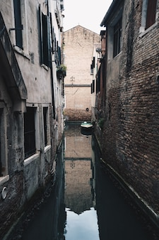 Rio estreito pequeno correndo jogar uma cidade suburbana entre edifícios de tijolos