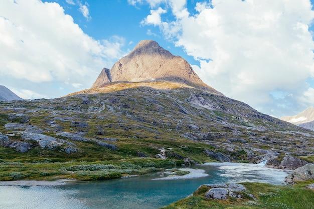 Rio fluindo abaixo da paisagem da montanha rochosa