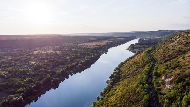 Rio fluindo entre uma colina com encosta coberta de vegetação e vila