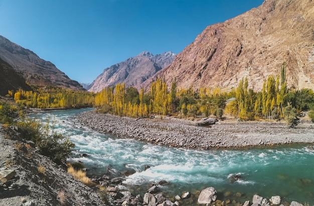 Rio gilgit que flui através de gupis, com uma visão da cordilheira e árvores no outono.
