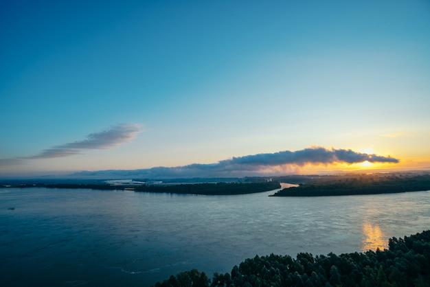 Rio largo. margem do rio com floresta e nevoeiro. brilho laranja do amanhecer refletido na água. sol brilha através da nuvem de forma de cobra ou crocodilo. paisagem atmosférica de manhã mística de natureza majestosa.