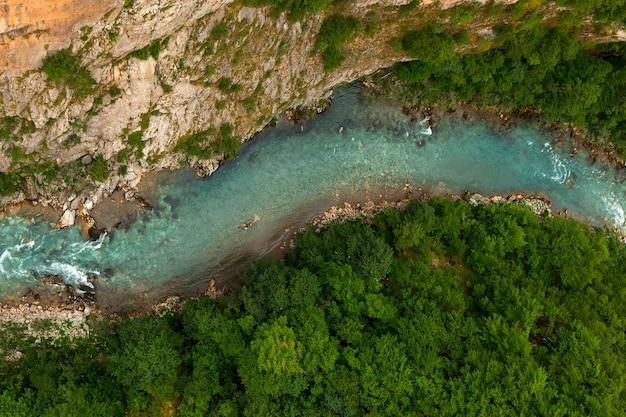 Rio lindo de montanha com águas azuis límpidas, no meio da mata e de pedras. natureza intocada natural. vista do topo.