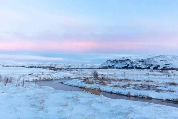 Rio na planície da islândia. as margens estão cobertas de neve