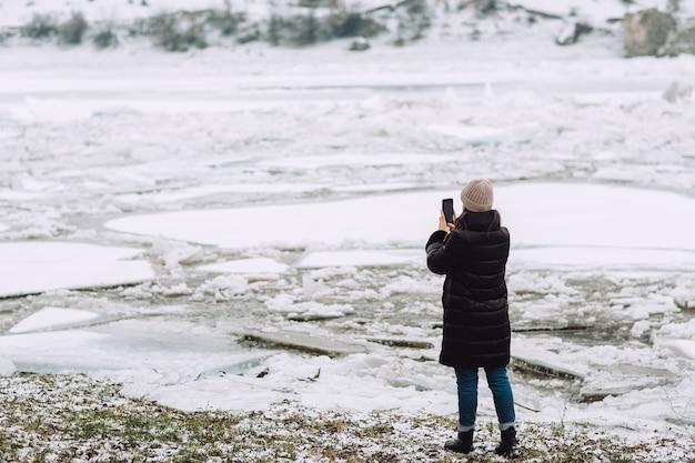 Rio no inverno com uma superfície coberta por uma espessa camada de gelo rachado e blocos de gelo. garota tira foto.