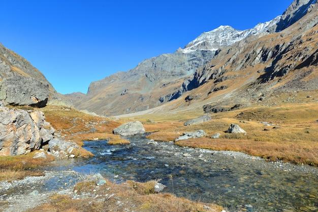 Rio no vale alpino e vista na montanha rochosa sob o lindo céu claro