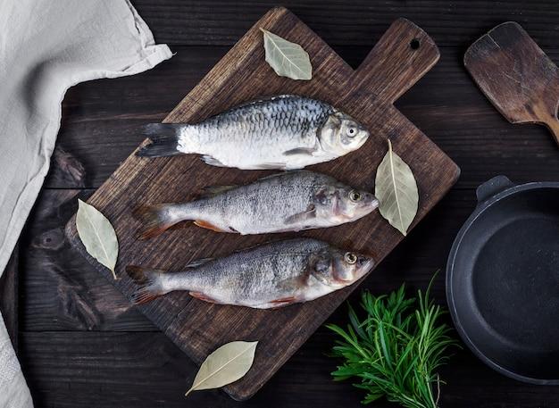 Rio peixe crucian e poleiro em uma placa de madeira marrom