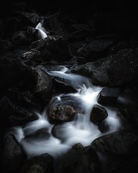 Rio pequeno bonito que atravessa rochas em uma floresta