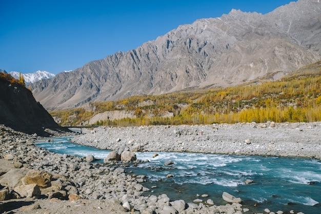 Rio que corre através do vale no outono contra a cordilheira de karakoram.