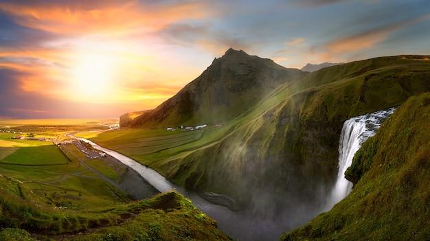 Rio que desce de uma cachoeira na islândia cercado por montanhas ao pôr do sol