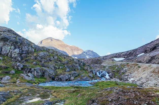 Rio que flui através da paisagem da montanha da rocha no verão