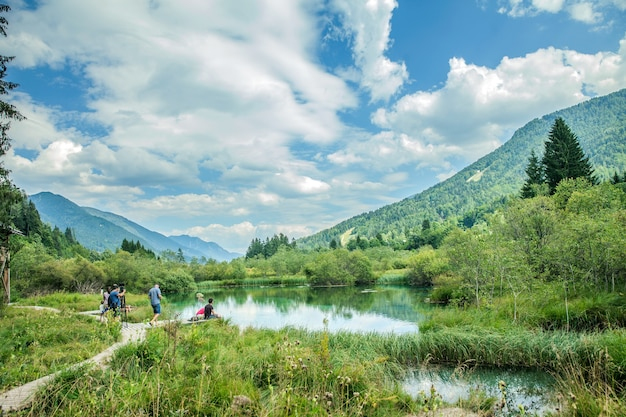Rio sava dolinka e alguns turistas na reserva natural zelenci em kranjska gora, eslovênia