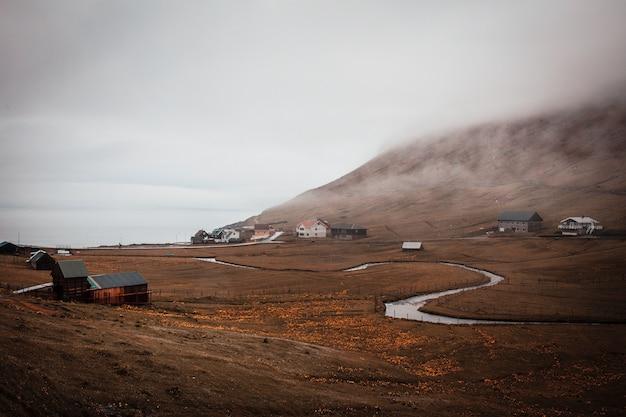 Rio sinuoso e vila costeira solitária envolta em nevoeiro na faroé