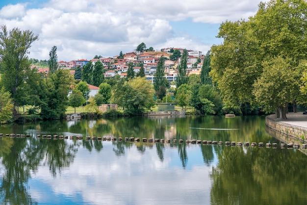 Rio tâmega, água calma, lugar de lazer, passagem de pedra sobre o rio chávez, paisagem urbana com árvores frondosas paisagem relaxante