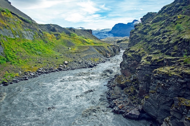 Rio tempestuoso da montanha flui das geleiras na islândia.