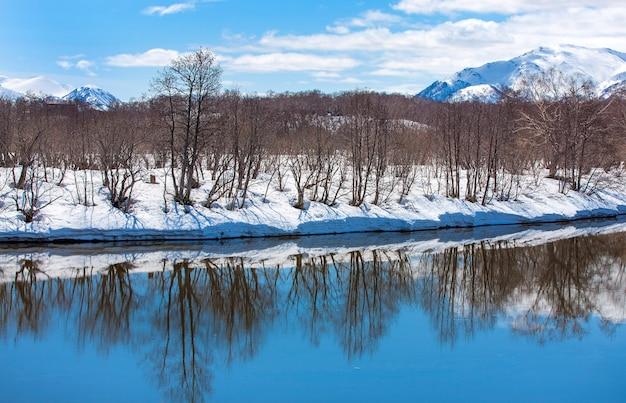 Rio, vulcão, floresta coberta de neve e céu azul no início da primavera