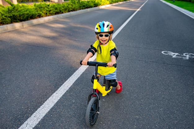 Rir criança em um capacete protetor e óculos de sol em uma scooter na estrada