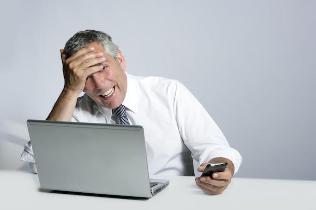 Rir homem de negócios sênior gesto de telefone de computador