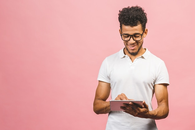 Rir jovem afro-americano masculino segurando um touch pad tablet pc isolado contra o fundo rosa