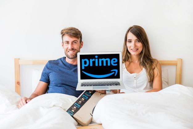Rir macho e fêmea na cama com laptop