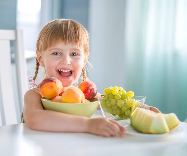 Rir menina com pêssegos, uvas e melancia na mesa