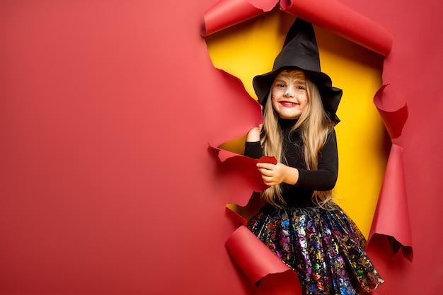 Rir menina criança engraçada em uma fantasia de bruxa no dia das bruxas