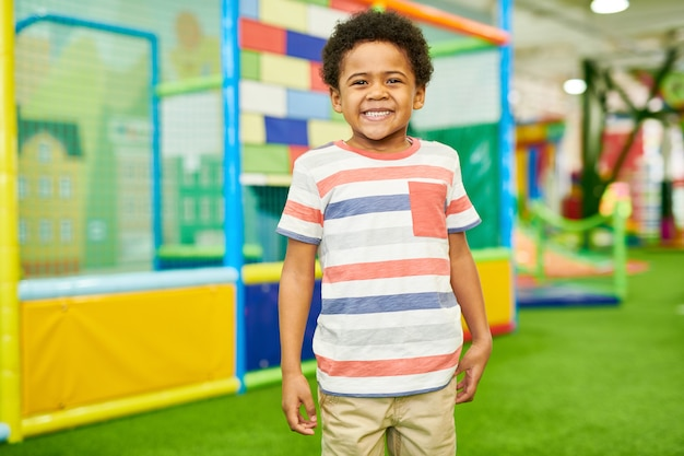 Rir menino afro-americano no play center