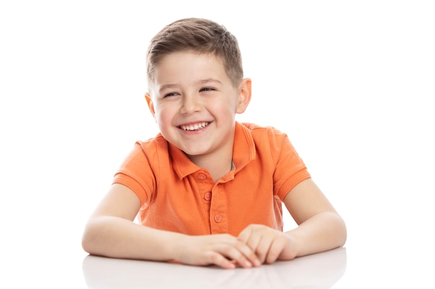 Rir menino em idade escolar em uma camiseta polo laranja brilhante senta-se à mesa. isolirvoan em um fundo branco.