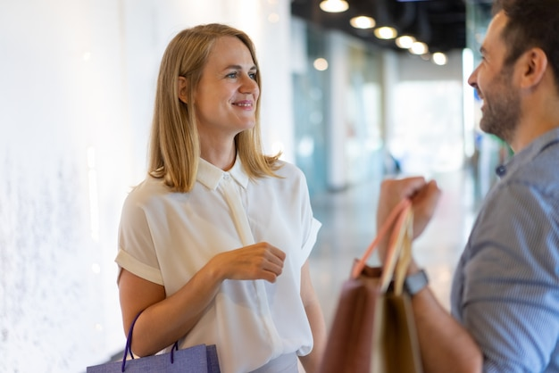 Rir, middle-aged, mulher, e, homem, conversando, shopping, e, segurando, sacolas papel