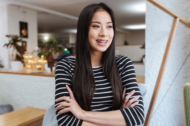 Rir mulher asiática com os braços cruzados na cantina