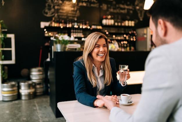 Rir mulher e homem de mãos dadas enquanto desfruta de café