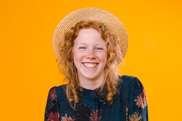 Rir mulher ruiva encaracolado em estúdio com fundo brilhante