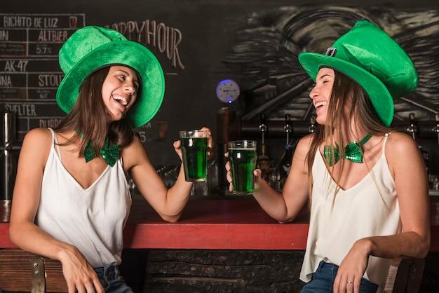 Rir, mulheres jovens, em, são, patricks, chapéus, segurando, copos bebida, em, barra, contador