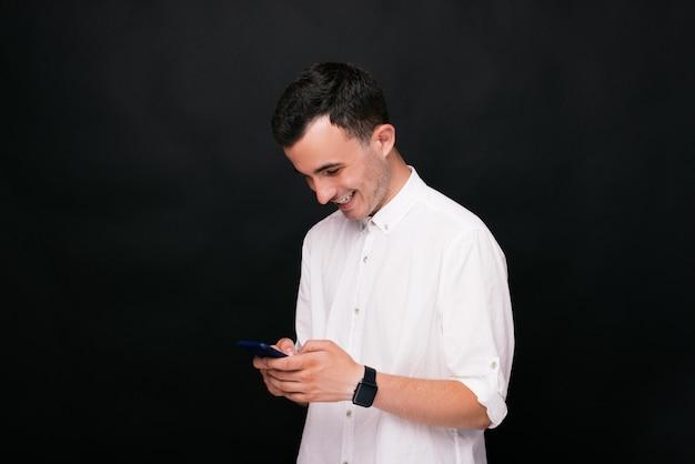 Rir ou sorrir menino está digitando uma mensagem e olhando em seu telefone.