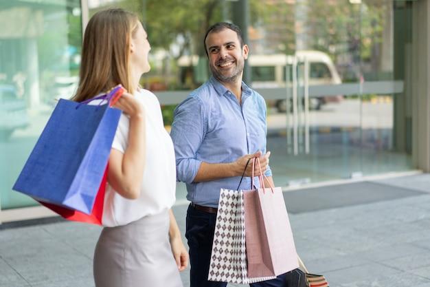 Rir, par, shopping, segurando, sacolas papel, andar, e, olhando um ao outro
