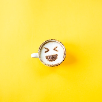 Risada do emoji é desenhada em uma xícara de café cappuccino
