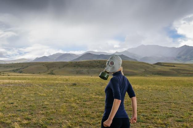 Risco de desastre ambiental. conceito de poluição, apocalipse. ar poluído, problemas ecológicos. mulher forte na máscara de gás militar no fundo das montanhas de nevoeiro.