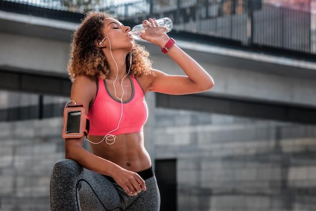 Risco de desidratação. mulher bonita e agradável bebendo água enquanto está com muita sede