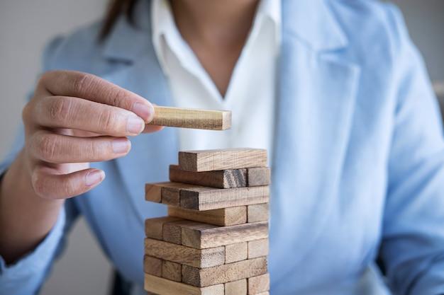 Risco e estratégia alternativos nos negócios, mão da mulher de negócios inteligente que joga colocando a hierarquia de blocos de madeira na torre para o planejamento e desenvolvimento para obter sucesso