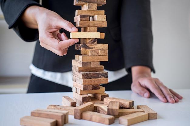 Risco e estratégia alternativos nos negócios, mão da mulher de negócios inteligente que joga colocando a hierarquia de blocos de madeira na torre para o planejamento e desenvolvimento