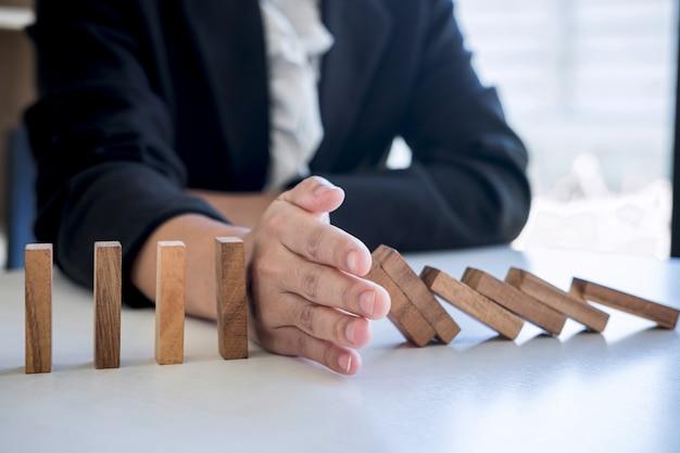 Risco e estratégia nos negócios, imagem da mão que interrompe o efeito de dominó de blocos de madeira, do bloco derrubado contínuo, prevenção e desenvolvimento à estabilidade