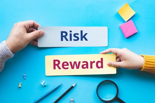 Risco e recompensa com texto em papel bolha e pessoa manual. investimento e gestão