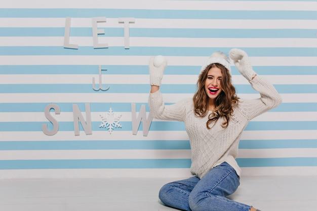 Riso alegre com sorriso deslumbrante, alegra-se como uma criança jogando bolas de neve e posando contra a parede com inscrição festiva para retrato feminino