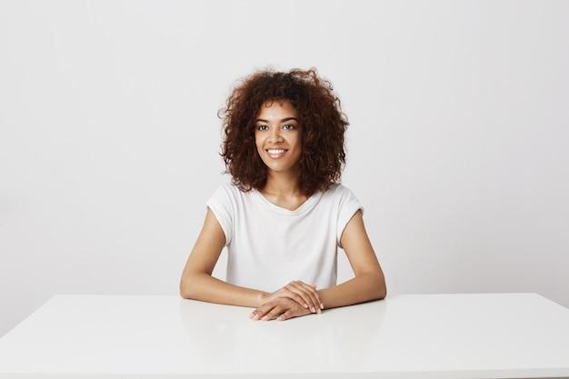 Riso de sorriso da menina africana bonita que senta-se sobre o espaço branco da cópia da parede.