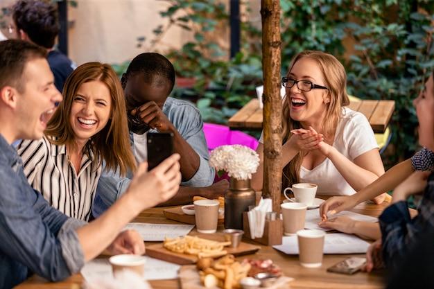 Riso sincero e mostrando imagens no smartphone na reunião casual com os melhores amigos no terraço do restaurante