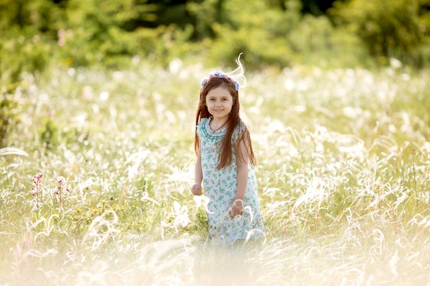 Risos felizes da menina atravessa o campo no verão