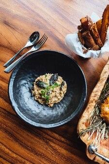 Risoto com cogumelo, erva fresca e queijo parmesão na placa preta na tabela de madeira.