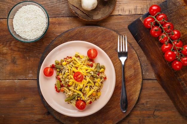 Risoto com cogumelos e queijo em um fundo de madeira perto de arroz e legumes.