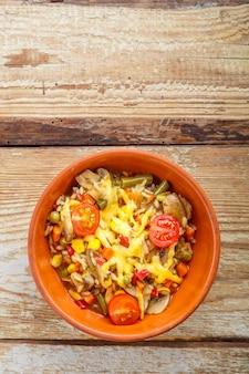 Risoto com cogumelos e queijo em um prato de barro em um fundo de madeira.